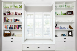Concept Cabinets has framed this bedroom window seat with prefinished board open shelf units and base cupboards with shaker style doors and drawers