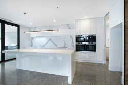 Kitchen with 2 Pac painted doors with finger pulls, 40mm stone top to the rear bench and 60mm stone top to the island with water fall end