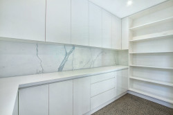 Butlers pantry with 2Pac painted doors with finger pulls and open shelving in prefinished board